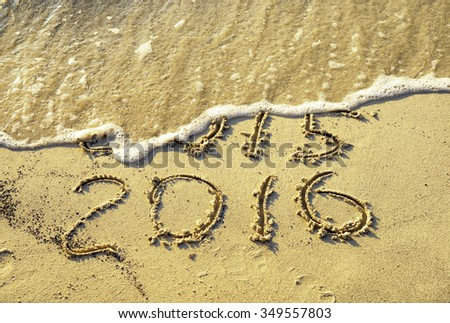 Old and new year written on the beach