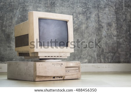 old and obsolete computer set on the floor with grunge concrete wall background, vintage color tone