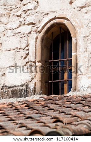 Old and red tiled roof with a grilled window - stock photo