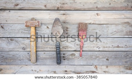 Old and rusting carpentry tools set on wooden background texture