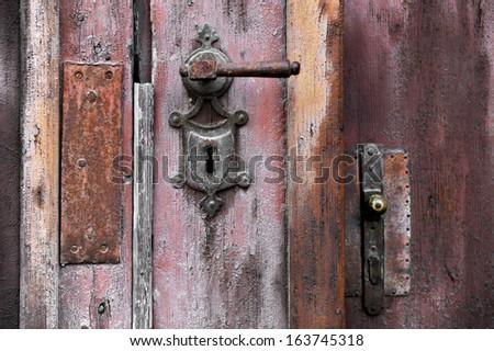 Old and rusty door handle and door lock - stock photo