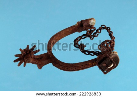 old and rusty riding spur on blue background. - stock photo
