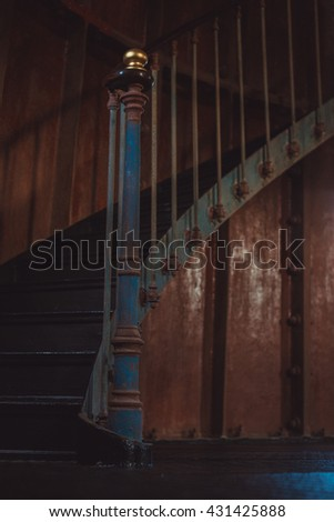 Old and rusty spiral stairs inside dark and gloomy room - stock photo
