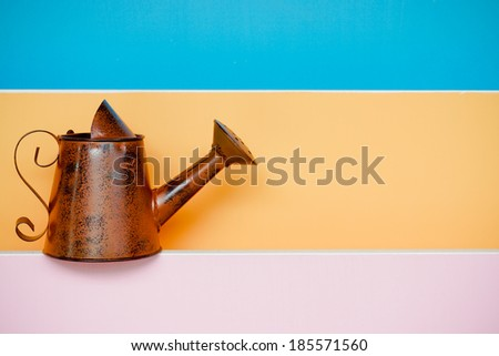 old and rusty watering can with colorful wood background - stock photo