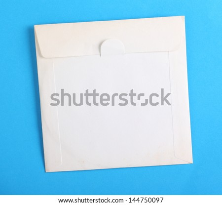 Old and stained blank white paper envelope used to store a compact disc on a plain blue paper background, with copy space