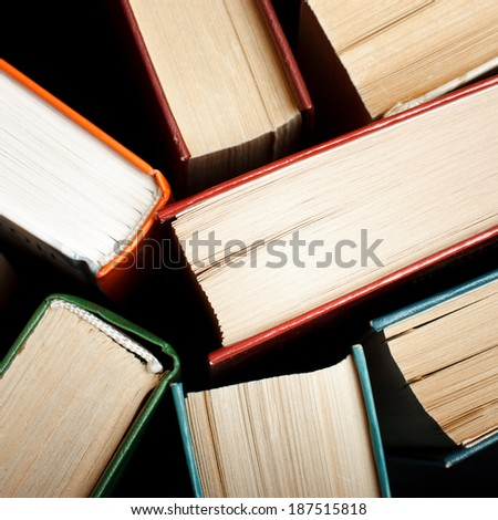 Old and used hardback books or text books seen from above. Books and reading are essential for self improvement, gaining knowledge and success in our careers, business and personal lives - stock photo