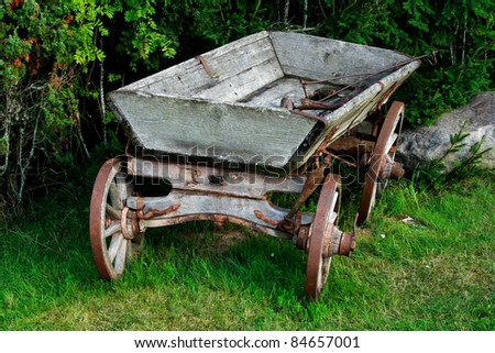Old and used wagon standing near green bushes - stock photo