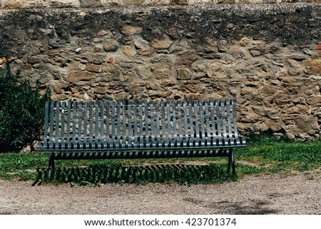Old and vintage bench in front of stone wall. - stock photo