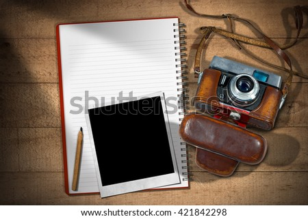 Old and vintage camera with leather case, empty notebook with pencil and an instant photo frame on a wooden table - stock photo