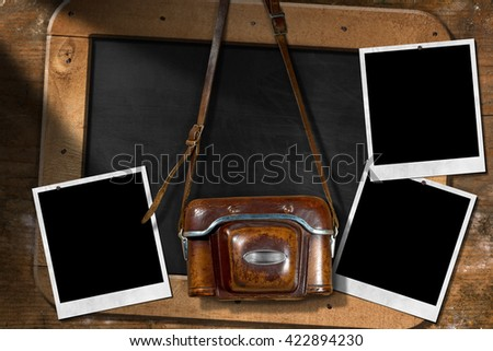 Old and vintage camera with leather case, three empty instant photo frames and a blank blackboard with wooden frame - stock photo