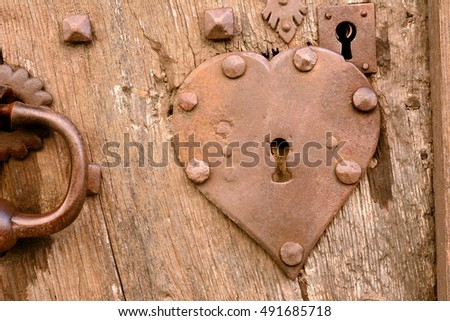 Old and weathered wooden door with rusted heart shaped iron key hole