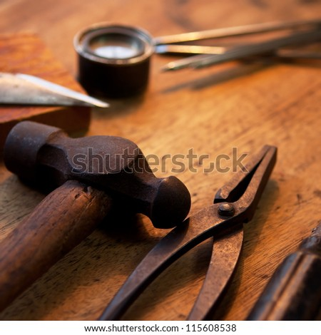 Old and well used hammer, pliers and screw driver on a old wooden desk. With warm incandescent  lighting. - stock photo