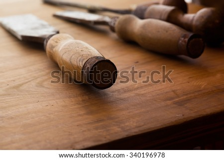 Old and well used wood carving chisels, on a old workbench. Old chisel with an oak handle. Shallow depth of field. - stock photo