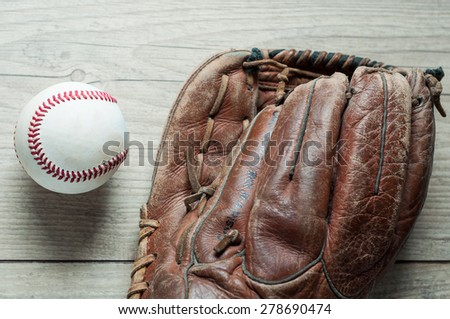 Old and worn used leather baseball sport glove over aged - stock photo