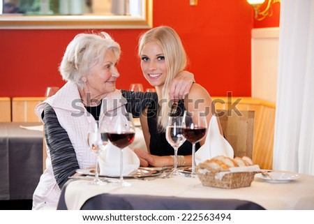 Old and Young Blond Women at Table Having Snacks at the Restaurant with Wine, Water and Bread on the Table.