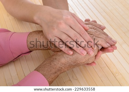Old and young hands. Hands of the old woman - 80 years covered with young hands - stock photo