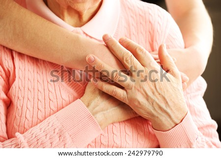 Old and young hands hug, closeup