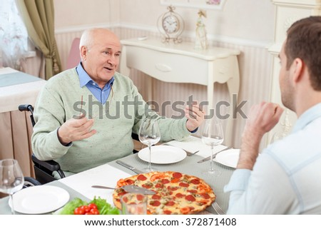 Old and young men have a dinner in restaurant - stock photo