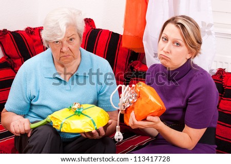 old and young woman are getting uninspired gifts - stock photo