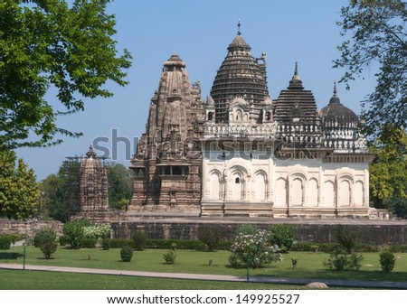 Old and younger Hindu temple, built by Chandela Rajputs, at Western site in India's Khajuraho framed by trees. White grey for the younger and older beige structure against blue skies over green grass.