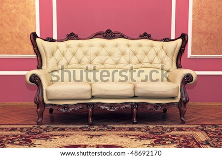 Old antiquarian sofa about a wall