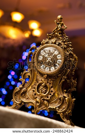 old antique clock with angel figurines over Christmas tree bokeh background - stock photo