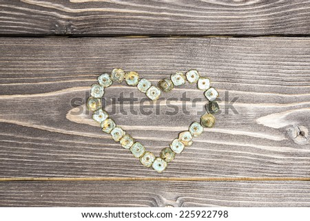 Old antique non-ferrous nails with patina on a dark wooden background in a shape of heart. Useful for love cards for Valentine's day  - stock photo