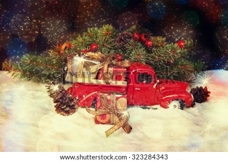 Old antique toy truck carrying a Christmas gift box.