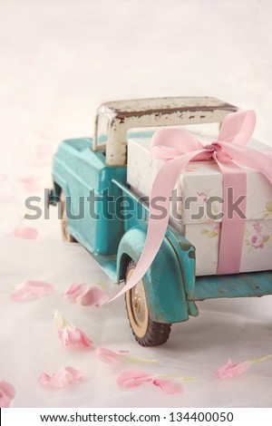 Old antique toy truck carrying a gift box with pink ribbon on romantic lace background and flower petals - stock photo