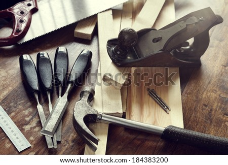 Old antique woodworking or carpentry tools on a hardwood floor concept for construction or repairing - stock photo
