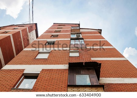 old apartment block of brick rise up in the blue sky