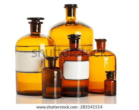 Old apothecary bottles of different sizes isolated on white background - stock photo
