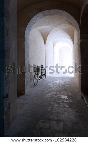 Old arcade and a bicycle leaning against the wall - stock photo