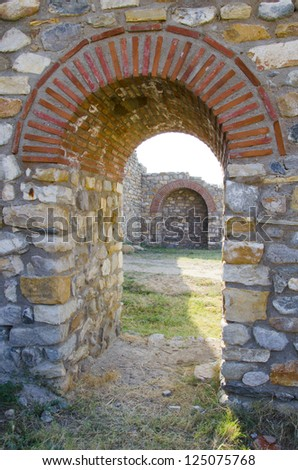 Old arched stone passage in the ancient town citadel ruins - stock photo