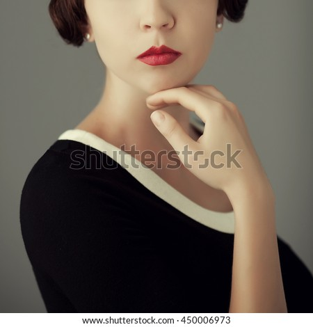 Old aristocracy concept. Close up portrait of posing young woman in black dress with her hand over gray background. Vintage hairdo. Studio shot