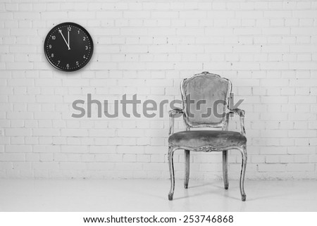 Old armchair against brick wall with clock. Converted in B&W - stock photo