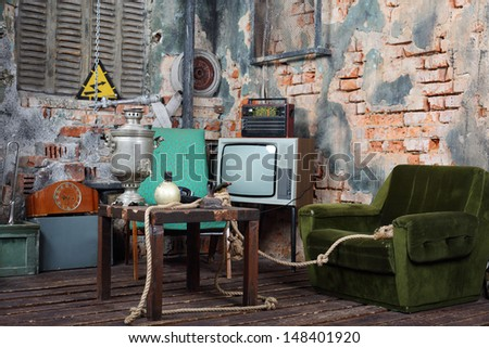 Old armchair, television, radio and table with samovar in very old house. - stock photo