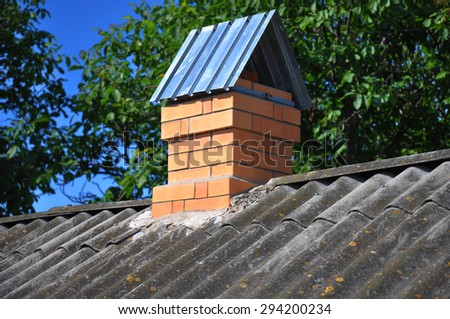 Old asbestos roof with new brick chimney. Roof repair - stock photo
