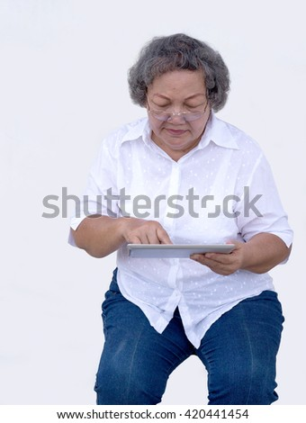 old asian grandmother watch and touch tablet on white background