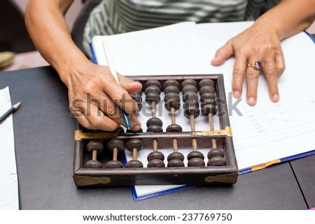 Old asian woman hands accounting with the old abacus - stock photo