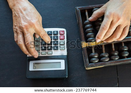 Old asian woman hands accounting with the old abacus and calculater - stock photo