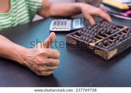 Old asian woman hands accounting with the old abacus and calculator - stock photo
