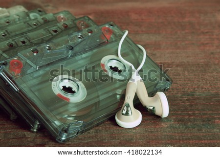 old audio cassettes lying with ear headphones on the brown wooden background