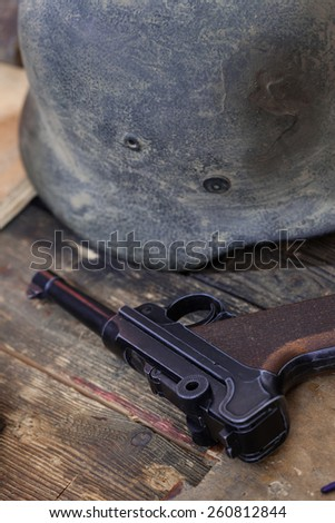 Old automatic pistol Parabellum and vintage German soldier helmet - stock photo