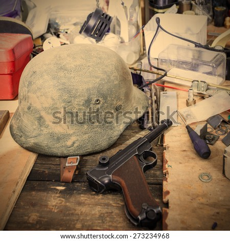 Old automatic pistol Parabellum and vintage German soldier helmet in the restoration workshop. instagram image retro style - stock photo