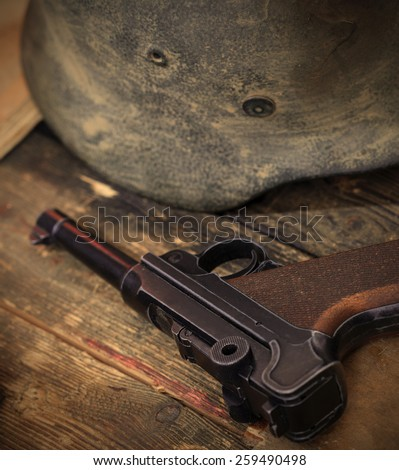 Old automatic pistol Parabellum and vintage German soldier helmet. instagram image retro style - stock photo