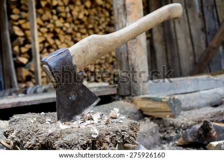 Old axe stuck in log and wooden tree logs ready for chopping in front of a staple of firewood. - stock photo