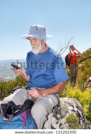 Old backpacker sending sms sitting on rock. Shot in Helderberg Mountains Nature Reserve, near Somerset West/Cape Town, Western Cape, South Africa. - stock photo