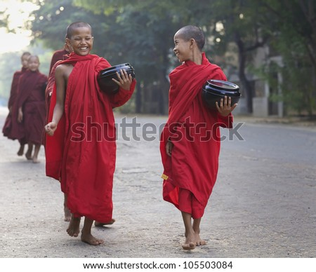 OLD BAGAN, MYANMAR- OCT 15: Two unidentified young novice monks walking morning alms in Old Bagan, Myanmar on October 15, 2011. 89% of the Burmese population is Buddhist. - stock photo