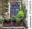Old balcony overgrown with flowers and green plants at summer time - stock photo